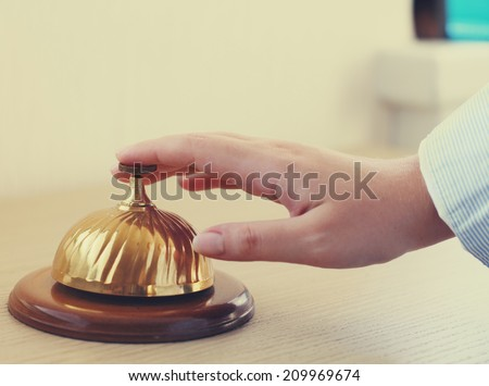 Hand of a woman using a hotel bell in retro style - stock photo