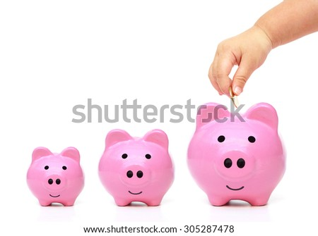 hand of a young baby giving golden coin to three piggy banks with different sizes - stock photo