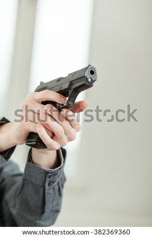 Hand of a Young Boy Holding a Real Hand Gun Pointing Away at the Camera - stock photo