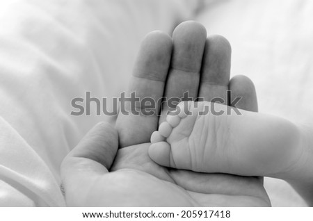 Hand of a young father touch his newborn baby foot (4 week old).(BW) copyspace,  Concept photo of newborn, baby, mother, motherhood, parenting and lifestyle
