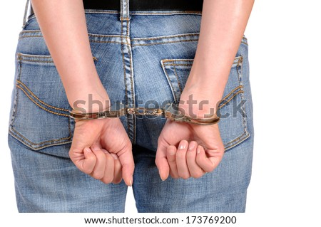 Hand of a young woman in handcuffs - stock photo