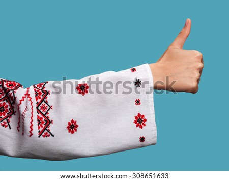 Hand of a young woman in the Ukrainian national clothes shows symbol ok with thumbs up on blue background. Embroidered shirt.