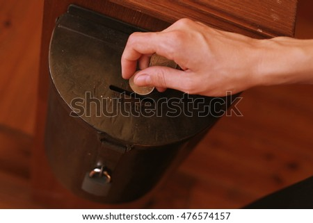 Hand of a young woman throwing coins into a donation box. Donation concept.