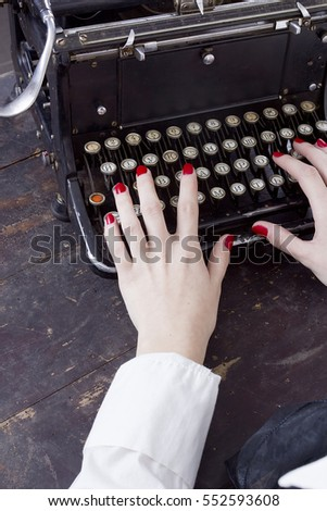 Hand of a young woman writer writing on antique typewriter