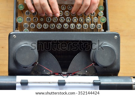 Hand of a young woman writer writing on antique typewriter. Above view - Type Writing Concept - stock photo