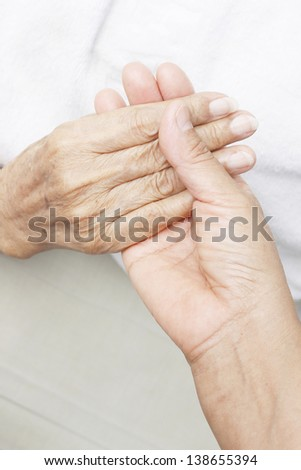 Hand of a younger woman holding the hand of an elderly woman.