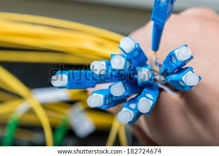 hand  of administrator holding bunch of optic fiber cables with connectors - stock photo