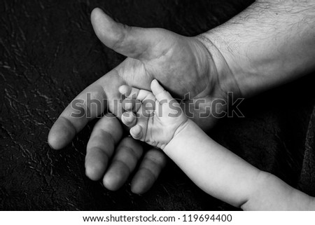 hand of an adult and  child in dark vein