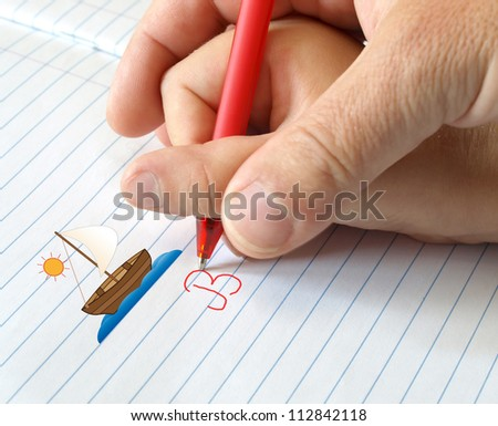 hand of an adult who teaches the child to write - stock photo