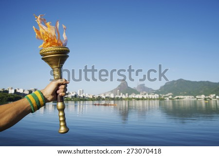 Hand of an athlete wearing Brazil colors sweatband holding sport torch against Rio de Janeiro Brazil skyline with Two Brothers Mountain - stock photo