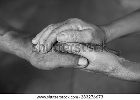 Hand of an elderly woman holding the hand of an elderly man. black and white.