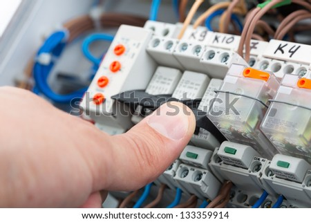 Hand of an electrician turning on a fusebox - stock photo