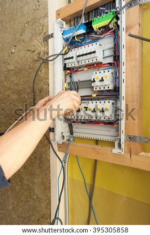 Hand of an electrician with screwdriver at an electrical switchgear cabinet - stock photo