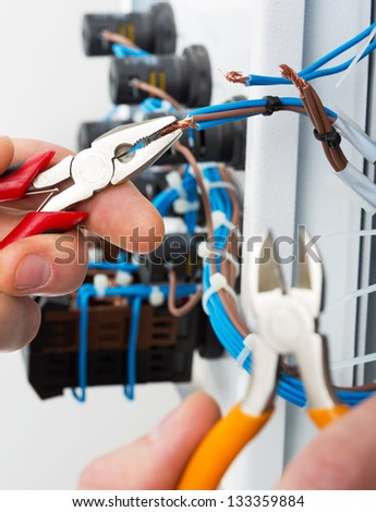 Hand of an electrician with tools at an electrical switchgear cabinet - stock photo