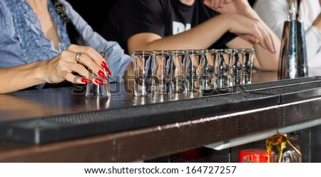 Hand of an elegant woman with beautifully manicured red nails holding an empty shot glass with a row of full glasses alongside lined up on the bar counter