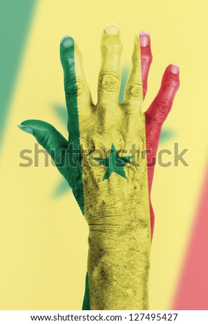 Hand of an old woman wrapped in flag of Senegal