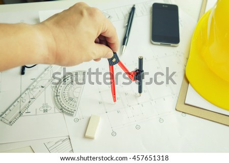 hand of architect drawing on architectural project,Projecting with pencil on the urban drawings. home planning on blueprint ,Architectural plans design home, on the desk, selective focus,vintage color - stock photo
