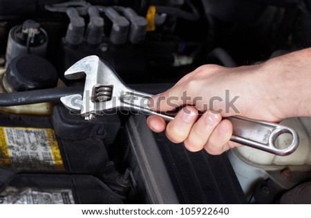 Hand of auto mechanic with a wrench. Car repair. - stock photo