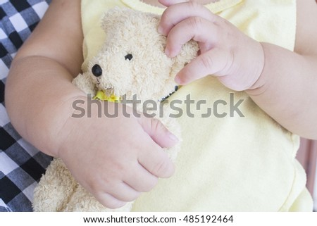hand of baby holding toy teddy bear playing
