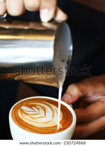 hand of barista making coffee pouring milk making latte art  - stock photo