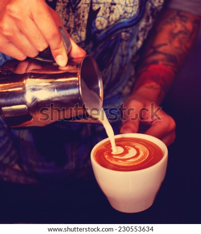 hand of barista making coffee pouring milk making latte art in retro filter effect lighting  - stock photo