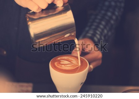hand of barista making latte or cappuccino coffee pouring milk making latte art,retro filter effect - stock photo