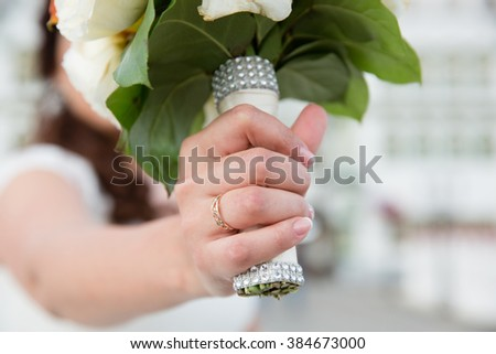Hand of bride with wedding ring on wedding bouquet - stock photo