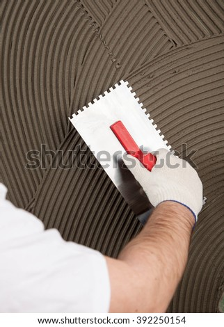 hand of builder worker  plastering  at wall - stock photo