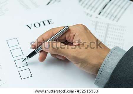 Hand of business man holding a pen trying to vote in paper - stock photo
