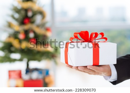 Hand of business person holding a gift for the New Year - stock photo