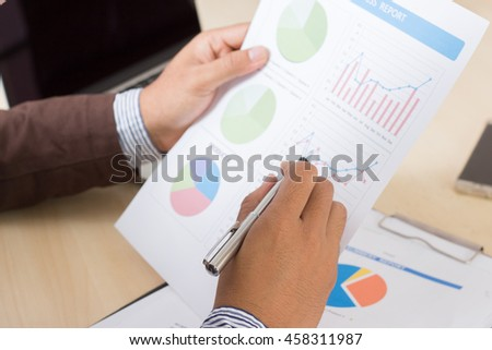 hand of Businessman and marketing statistic with money graph, data gathering and market analysis.