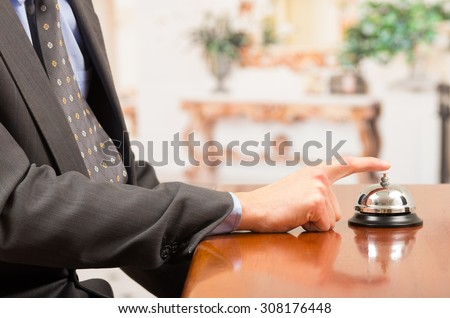 hand of businessman customer ringing hotel bell in reception desk close up selective focus - stock photo