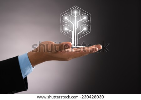 Hand of businessman holding digital tree: ecology and technology concept - stock photo
