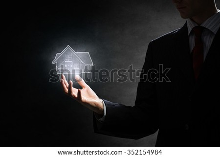 Hand of businessman holding glowing house model on dark background