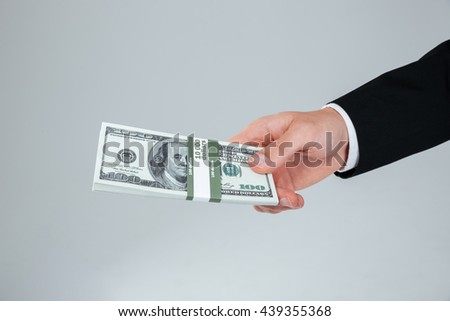 Hand of businessman in suit holding money over white background - stock photo