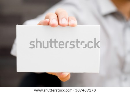 Hand of businessman showing white paper - stock photo
