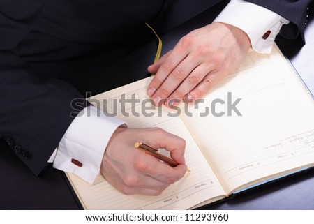 Hand of businessman taking notes at board meeting