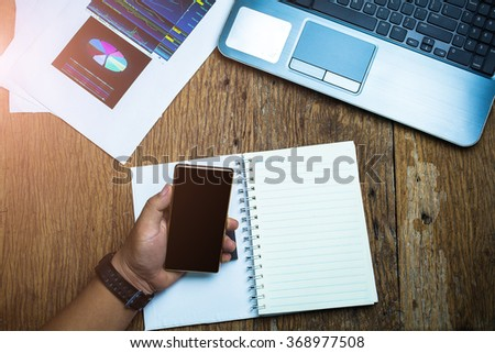 Hand of  Businessman to use a smartphone - stock photo
