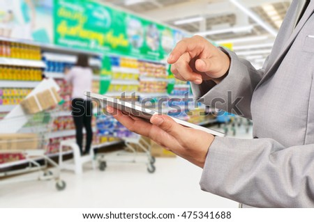 Hand of Businessman use Mobile Tablet in supermarket with Blur Background of Staff arrange product display on shelves in Supermarket or Hypermarket