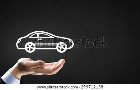 Hand of businessman with car against gray background - stock photo