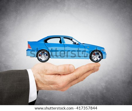 Hand of businessman with lovely blue car on grey background