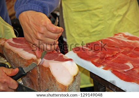 hand of butcher and knife during preparation of raw ham - stock photo