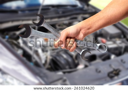 Hand of car mechanic with wrench. Auto repair garage. - stock photo