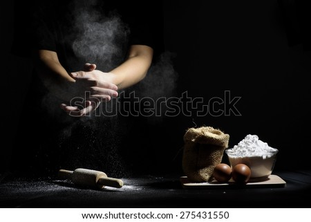 hand of chef clap a flour with wooden rolling pin and ingredients on black background - stock photo