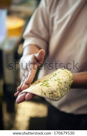 Hand of chef making naan - stock photo