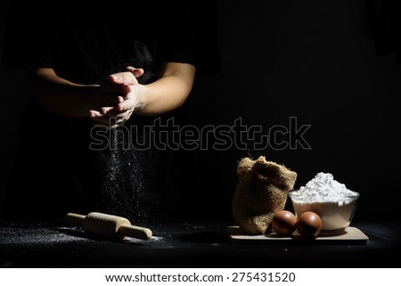 hand of chef thresh flour with wooden rolling pin and ingredients on black background - stock photo