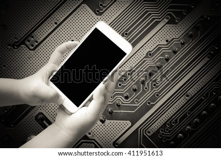 hand of child holding mobile phone with board circuit background