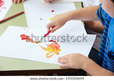 Hand of child painting with brush and color in a kindergarten - stock photo