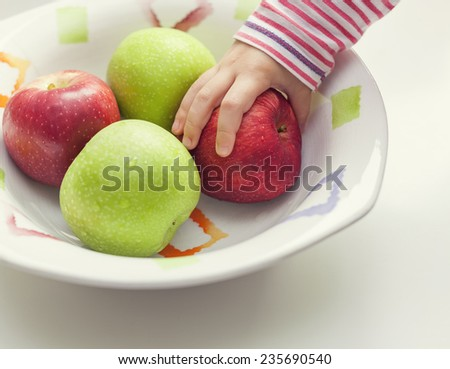 hand of child taking apple from bowl - stock photo