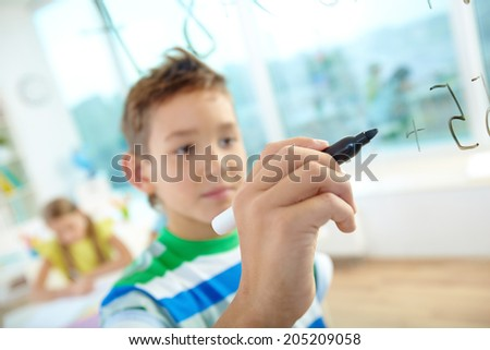 Hand of clever boy doing sums on transparent board with schoolmate on background - stock photo